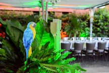 Corporate Jungle Fever Event / We created a jungle-like atmosphere with the use of greenery and uplighting in green and golden hues. Props that complimented the styling perfectly, a large cheetah and tropical birds scattered throughout, rustic styled signage. Tables lined with Cheetah print table runners, gold and willow green tealights with willow pintuck napery. Each table had a centerpiece of lush tropical leaves cascading from vases. Corporate Theming. Youtube: https://www.youtube.com/watch?v=u6qaGlG1ZVM&feature=youtu.be