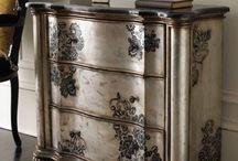 Cómoda antigua patinada en color madera con cajones en blanco semi plateado y flores grises pintadas en los cajones
