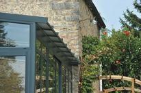 Véranda Rideau - Architekt / Avec toiture débordante, sans chéneau. La véranda Architekt est d'une allure indémodable qui fait la part belle au vitrage et apportera éclat à votre pièce de vie. Aussi, son style « atelier » peut aussi bien s'adapter à une maison de campagne en pierre, qu'à un pavillon auquel on souhaite donner une touche de modernité.