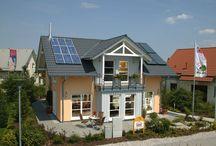 """Musterhaus Poing - Bavaria / Unser """"bayrisches"""" Musterhaus nahe München überzeugt durch die für die Region typische Architektur. Hoher Kniestock, flache Dachneigung, ausladende Dachvorsprünge und die Liebe zum Baustoff Holz charakterisieren das schmucke Einfamilienhaus. Das offene, von Holzböden und Sichtbalken geprägte Erdgeschoss zieht jeden Besucher in seinen Bann. Im Dachgeschoss ermöglicht der hohe Kniestock eine maximale Nutzbarkeit der Räume."""