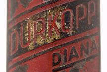 Diana of Blansko / A small, enamelled plate used to depict the brandname of the bicycle, ornamented with domed motifs. It is attached to the so-called bicycle-neck under the front part of the handlebar, with the help of rivets through the bore-holes on the two corners of the tiny device.
