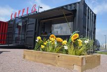 Coffi Co. - Container Cafe by ISOSpaces / Converted from two joining containers (20ft & 40ft), this is Coffi Co's quirky new coffee shop located in Cardiff Bay. The bi-folding glass doors allows the space to completely open up and extend the internal space.  Cardiff Bay - Wales, UK