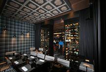 Restaurant « Pléthore & Balthazar » – LYON / Aspect extérieur et intérieur de l'armoire cave à vin : Mur de cave façade noir et tôle vieillie. Aménagement intérieur : casiers dans lesquels 1 bouteille en présentation debout en façade et stockage bouteilles couchées à l'arrière.  Façade : Portes coulissantes  Capacité : environ 480 bouteilles