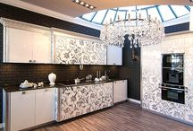 """Кухня """"ЛЮЧИЯ"""" / Модель выполнена в стиле ар-деко с элементами классики. Такая кухня придает пространству выразительность и оригинальность. Фрезерованный рисунок на фасадах и массивный резной карниз покрыты серебряной поталью.  Размер кухни: 3942/770/2327h Размер пенала: 1968/602/2327h Фасады: МДФ, крашеный лакированый, фрезерованный рисунок с серебряной или золотой поталью Столешница: кварцевый камень Корпус: ЛДСП, белый"""