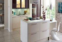 Get The Look > Modern Purple Gloss Kitchens / High Gloss Aubergine accent doors add a luxurious and sumptuous finish to your kitchen. Omitting warmth and personality, the rich purple hue effortlessly contrasts the soft cream doors, whilst the cleverly placed lighting illuminates a soft glow that highlights the precise edging of the counter top.