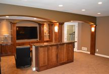 Pewaukee Basement Remodel / Our team built out walls to create entirely separate areas for this family, including a workout room, a media room, a game area, and bath and laundry areas. We replaced the existing stairs with new, custom stairs, and installed custom cherry columns and cabinets.   A unique swinging bookshelf provides access to the underside of the stair. The cabinets were accented with granite tops and a natural stone and glass backsplash.