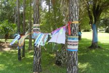"Fabric Bombing / My wonderful fiber art friends ""bombed"" my front yard with fabric, as a show of support during a difficult time.  The result was approximately 30 feet of prayer flags, banners, streamers, ribbons, and sheer fabrics swaying in the Florida breeze.  It was SO touching!  I greatly appreciated it.  (And I hope my neighbors didn't mind that I left it in place for a month!)"