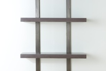 Stack Shelves / A customizable shelving system with crisp slabs of highly polished colored concrete that appear to float off the wall in front of a pair of vertical metal bars.