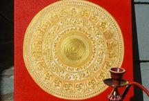 Mandala Om / Ом (санскр.) или Аум — в индуистской и ведийской традиции — сакральный звук, изначальная мантра, «слово силы». Часто интерпретируется как символ божественной триады Брахмы, Вишну и Шивы. Используется в практиках йоги и техниках медитации. В соответствии с ведийским наследием, считается, что звук Ом был первым проявлением не явленного ещё Брахмана, давшим начало воспринимаемой Вселенной, произошедшей от вибрации, вызванной этим звуком.  Материал:холст, акрил Мандалу можно сделать любых размеров, в любой цветовой гамме под Ваш интерьер, с любой вариацией узоров, срок изготовления от 3 до 5 дней (в зависимости от размеров)