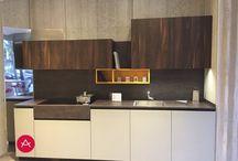 Cocina Materia de exposición / Colección de cocina con materiales naturales, a los que se añaden materiales técnicos e innovadores. La sensación al tacto es sedosa, con bases en laca super mate, y un bloque de mármol de grafito cepillado, hechos de un mayor espesor. El entorno eta formado por paneles de madera, acacia tratada térmicamente. Este material, también se utiliza para las columnas a una mayor altura de la planta con techo de hornos integrados.