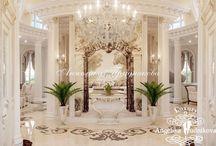 Дизайн проект интерьера загородного дома в Классическом стиле в г.Краснодар / Дизайн загородного дома в городе Краснодар выполнен в классическом стиле. Основными цветами дизайна являются бежевый, коричневый и белый. В гостиной открытого типа имеется комфортабельная мебель и столовая зона. Мебель, люстры, обои, картины и светильники создают неповторимую атмосферу статности и роскоши.