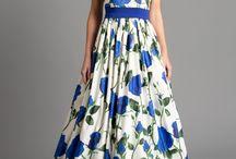"""Abendkleid mit Blauen Rose, Maxikleid Blau/Weiss / Das Abendkleid """"Diana"""" ist aus natürlicher Baumwolle gefertigt worden, um der Trägerin gerade im Sommer eine hohe Atmungsaktivität des Materials zu offerieren. Aufgrund der Verarbeitung von Satin im Kleid besticht dieses durch einen leichten Glanz, welcher die großen blauen Rosen noch besser in den Vordergrund stellt. Tragen Sie das liebevoll gestaltete Kleid zur Cocktailparty oder auf der Hochzeit Ihrer besten Freundin und beeindrucken Sie andere Menschen mit Ihrem exquisiten Geschmack."""