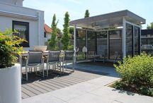 moderne stadstuin / Achtertuin met een moderne en comfortabele inrichting. Een royaal terras van keramische tegels met de aangrenzende overkapping geven de tuin veel sfeer