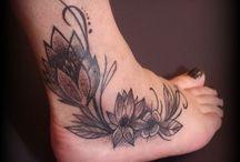 tatouage pied / tatouage sur pied et cheville, inspiration japonaise (fleur de lotus et fleurs de cerisier japonais) et champêtre (pâquerettes, jonc et fleur de lys), avec effet dotism pour les ombrages. tatouages pied et cheville femme, tatouage dégradé de noir
