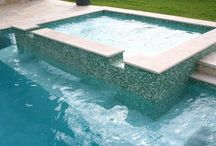 Water Feautures - Spas & Waterfalls / Many raised perimeter-overflow spas are finished in all glass tile. This creates a brilliant luster in the sunlight and can be further enhanced by pool lighting during the evening.