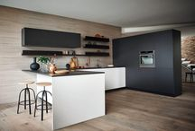 Maxima 2.2 - Light silk-effect Bianco lacquer Bronzite melamine / Peninsula unit: doors with Hook grip edgings in light silk-effect Bianco lacquer. Pietra Brown laminate worktop. Tall units: push-pull opening doors in Bronzite melamine.