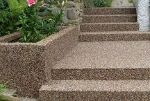 What is resin bound stone surface? / The resin bound stone creates a long-lasting, even, anti-slip, permeable surface. It is achieved by carefully coating each stone with clear resin. Each stone can have a different shape and colour and covering them with resin not only keeps them together, but also protects them.