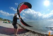Kitesurfing / Czy już wiesz czym jest kitesurfing? To sport, w którym wykorzystuje się moc wiatru i niezwykłą siłę wody. Wystarczy latwiec i deska, by móc zasmakować tej niezykłej przygody! Wszystkim, którzy mają odwagę spróbować tego sportu proponujemy kursy, które rozpoczynają się już 28 kwietnia 2013.