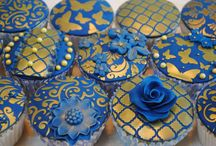Royal blue and gold stencilled cupcakes / A selection of blue and gold themed cupcakes made for Create & Craft TV using four of our Cake Crafting stencils in the following designs: Trellis, Butterfly, Vintage Flock & Ornate Swirls.