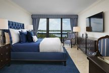 Luxe Palm Beach Residence / Luxury palm beach apartment overlooking the inter-coastal and ocean. wrap-around terrace. Plush sectional in vibrant blue with tan accents. Custom window treatments wrap the room with warmth.