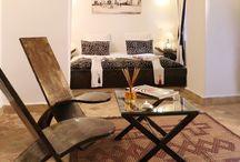 Suite double luxe au Riad Anyssates / Ariane avec un accès direct sur le grand patio et la piscine est décorée avec des meubles en acier brossé lisse. Le coin chambre, lové dans une grande alcôve est agrémenté de peintures d'artistes locaux. Les tons beige et marrons s'harmonisent avec la salle de bains en tadelakt chocolat.