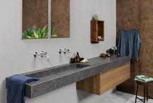 Urban Jungle Badkamer trend / In de badkamer creëer je deze rauwe urban sfeer eenvoudig. Combineer tijdloos wit sanitair met materialen als blauwstaal, stoer graniet of een sleetse beton look. Een stevig accent in hout geeft leven. Laat koperen leidingen zoveel mogelijk in het zicht en style met vintage ogende metalen manden voor handdoeken. Met de trendkleur blauw, de kleur van de traditionele werkmanstof denim, geef je een subtiel gevoel van luxe aan de sobere basis van zwart, grijs en wit.