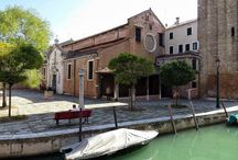 """Chiesa di San Nicolò dei Mendicoli / San Nicolò dei Mendicoli is a church in the sestiere or neighborhood of Dorsoduro in Venice. The islet where the original church was located previously housed poor fishermen, hence the addition of mendicoli (""""beggars"""") to the name of San Nicolò. From then on, the inhabitants were called Nicolotti. The present structure dates from about the 12th century, with frequent reconstructions. The present clock tower was added in 1764 to replace an older one."""