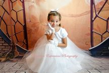 First Communion Dress Style 5139 / This first communion dress has it all. Satin and organza, tea length with cap sleeves and pretty flowr. Pearl button closure in the back with satin tie bow. Its fully lined and made in the USA. All this for only $49.95.
