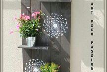 Estantería de madera pintada en gris y flores blancas para macetas