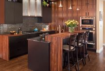 Life of the Party / The dazzling grain of Bolivian rosewood matched with marble countertops and glass cabinetry breathe life into this kitchen made for entertaining.
