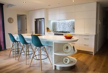 Melbourne Kitchen and Laundry / Our designer Michael has created something clean, classy and sophisticated to match the Melbourne based apartment. The walls beside the kitchen were already curved so creating a curved end to the island bench makes this kitchen look like it's always been there. Our clients Kirsty and Laurie wanted their kitchen to be white but didn't want to lose the homely, warm feel that can easily happen with a white kitchen so timber floors were laid to combat this.