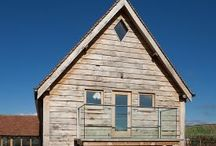 Venables Oak project: Famington Old Farm / Green oak frame using specially selected European structural grade oak beams, manufactured using traditional mortise and tenon joints. Building clad externally with fresh sawn feather edged rebated oak weatherboard cladding. Front entrance porch with double hammer beam feature truss. Curved wind braces to front frame. Ornate detailed ceiling detail with queen post trusses. Oak framed and boarded doors.