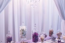 Elegant Purple Wedding Dessert Table / Draped in cascades of white curtaining, illuminated by a gorgeous, glistening chandelier, this candy bar was one that definitely impressed the crowds. Perfectly packaged sweets, with custom designed chocolate bars, and colour matching candy, it's no surprise this beautiful couple's day had all the exquisite elements to create a very special treat. Dessert Table. See the full film on our YouTube channel: https://youtu.be/91p-puqmn-k