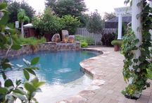 Starry Light Pool Design / 5 Star Outdoor Design custom built this one of a kind pool in Jacksonville, FL. Surrounding the pool are beautiful stones, a unique waterfall and a stone wall that runs along one side of the pool. But what makes this pool so amazing are the small lights on the bottom of it that change colors! As if the pool isn't cool enough this Jacksonville, FL home also features a custom built circular fire pit area and beautiful outdoor kitchen under one of the pergolas.