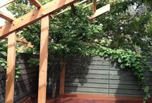 Rockridge Trellis, bench and deck / A front yard entertainment space with a freestanding Trellis, built in benches and an Ipe deck. The dark wood is contrasted with white river rocks and planting.