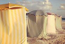 Lifes a Beach =====hut / Beach Huts since time began we've had a place on or very near the beach to go to The early days ladies were wheeled down to the sea and went into the water so as not to be seen These days they are a valuable asset in upmarket seaside places / by Dottie P