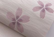 博多織「ひとひら」(Nagoya obi)/  博多経錦紬「天空」(Tsumugi (Pongee)) / OKANOのこの秋の新作紬「天空」は、献上柄を地紋に織り込みながら、整経暈しという手法で、先染めの経糸を微妙に変化させることにより、ぼかし織りによるグラデーションで空の色の移り変わりを表現しました。名古屋帯「ひとひら」は、よろけ風の動きのある地紋に、ポイント柄を配した博多織では珍しい一品です。