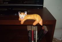 CAT SLEEPING on the edge, wood carved by EXTRAVAGANZA. / Wood carved cat, sleeping on the edge. Painted with acrylics colors. It is a funny statue to put in the border of a library, up of a TV (as you can see in the photo) or any table. It will make you and your friends smile many times...   Length: 20 cm. 7.87 inches. High: 10 cm. 3.94 inches. Width: 10 cm. 3.94 inches.