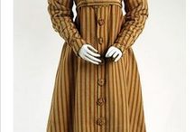History - Pelisse or Redingote / Redingote, or Pelisse, or Walking Dress, or Promenade Dress: Going by many names, this is a coat copied from men's overcoats but worn by both men and women. Generally, opens down the front, worn for warmth over a dress or coat and breeches, and has a military look with front vertical buttoning or decoration.
