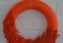 KAROTKA - 99 zł - wieniec / Minimalizm w pełni. Monochromatyczny wianek w ognistym kolorze pomarańczy. Wykonany z lekkich materiałów – włóczki misternie oplatającej bazę wianka i filcowych liści. Piękno w prostej formie.  Wianek jest w pełni trwały i może posłużyć także jako dekoracja okna, ściany lub stołu.  Doskonały pomysł na prezent.  Średnica ok. 29 cm.