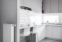 """Minimalizm i czystość formy / Kuchnia w kształcie litery """"U"""". Spokojny i czysty charakter kuchni to idealne rozwiązanie dla fanów minimalistycznych, pełnych naturalnego światła, surowych pomieszczeń. Wszechobecna biel bardzo dobrze współgra z odcieniami szarości. Stonowane kolory optycznie powiększają przestrzeń, która w takiej formie została optymalnie wykorzystana. Fronty białe, lakierowane z połyskiem z uchwytami frezowanymi. Blat Egger w odcieniu jasnej szarości. Zlew i okap Franke. Okucia Blum. Kosze Cargo."""