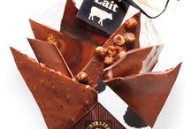 Nos Bouquets de Chocolat / Le Bouquet de Chocolats, vous connaissez ? Plus gourmand qu'un bouquet de fleurs et plus audacieux qu'une boîte de chocolats, le Bouquet de Chocolats fait le succès de l'Atelier depuis sa création par Serge Andrieu en 1995. Chocolats noirs puissants, blancs crémeux, au lait généreux... Dans un cornet coloré, il dévoile un assortiment de feuilles de chocolat maison choisies parmi 33 saveurs différentes.