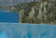 Swimming Pools / Piscinas interna y externa. Ambas climatizadas. La piscina al aire libre -420 m2- está conectada a la interna. El sector cubierto está ambientado con la roca y vegetación naturales de la zona. El espejo de agua de la piscina externa, desprovisto de borde, logra el efecto de infinito y se incorpora en la escena a la cancha de golf, los cerros, bosques y lagos.