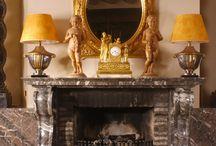 Klassieke interieurs / In een klassiek interieur vind je veel invloeden uit de Renaissance zoals ornamenten, zuilen en decoratief meubilair. Typerend voor deze statige en elegante woonstijl is luxe en overdaad. Symmetrie brengt hier balans in. Gouden en zilveren accessoires, zware gordijnen van velours, grote kroonluchters, donkere houtsoorten en massief natuursteen op de grond.