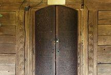 dintr-o lume în alta lume / Una din trăsăturile cele mai caracteristice, interesante și mai învăluite în mister ale bisericilor de lemn din România este limbajul sculptat al portalelor de la intrări. Portalele, la fel ca și gulerele și mânecile cămeșilor țărănești, au fost cel mai adesea locuri de trecere în plan atât fizic cât și simbolic. De aceea ele au fost protejate și investite cu multă atenție.   https://ro.wikipedia.org/wiki/Biserici_de_lemn_din_Rom%C3%A2nia