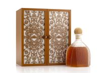 Patrón en Lalique : Série 1   packaging by MW Luxury Packaging / Patrón tequila - the decanter is presented in a wooden box, hand wrapped in high quality leather. The doors of the box feature panels of moonstone overlain with an intricate metal lattice, incorporating the Patrón Bee logo; bespoke hinges and clasps give the box a truly impressive antique effect. The bottle sits on a drawer which contains a decorative stopper, and a booklet telling the story of Patrón tequila.