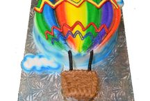 Hot Air Balloons / Every year in early October thousands of people from all over the world flock to Albuquerque to see hundreds of hot air balloons take to the sky. In celebration of this spectacular event, we create two sizes of balloon-shaped iced sugar cookies. The delicious poured fondant and royal icing give the balloon cookies the color we have come so accustomed to seeing in the sky this time of year.