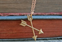 Pi Beta Phi / One, two, three words carved on a golden dart.