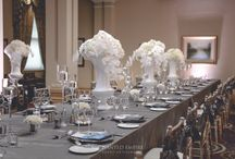 Silver + White Corporate Event / An opulent corporate dinner which consisted of a luxurious colour palette of silver and white.  With metallic glass charger plates, adorned with platinum satin napkins and custom pearlescent menus, framed each guest place setting perfectly. For that extra glamour, silver mirror plinths topped with white urns cascading in beautiful white hydrangeas and the crisp lines of Phalaenopsis orchids. A classic style, effortlessly transpired, for an evening of sophistication. Enchanted Empire