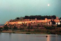 Badajoz / La ciudad más grande de la región se levanta sobre el Cerro de la Muela, rodeado por el Río Guadiana. En el siglo IX reinaba en Córdoba el emir Muhammad I, fue entonces cuando Ibn Marwan fundó Batalyaws con un marcado carácter defensivo. Fue capital de un poderoso reino Aftasí. Con las invasiones almohades y almorávides, Badajoz se fortificó aún más aunque Alfonso IX logró su conquista en el siglo XIII. Ciudad rayana, ha sido portuguesa en un par de ocasiones y se ha guerreado mucho por ella.